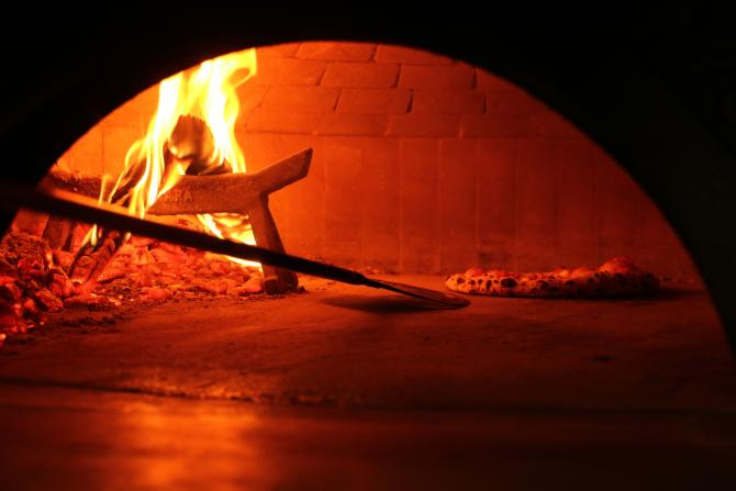 A delicious pizza finishes cooking in a brick oven pizza in Wichita