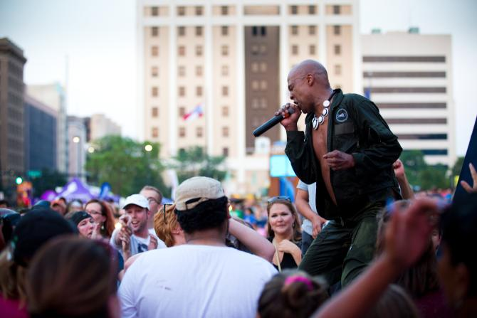 Lead singer for Fishbone screams into a mic in front of a large crowd on an outdoor stage at Wichita Riverfest