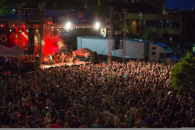 Flogging Molly perform at the Wichita Riverfest in front of a large crowd outdoors