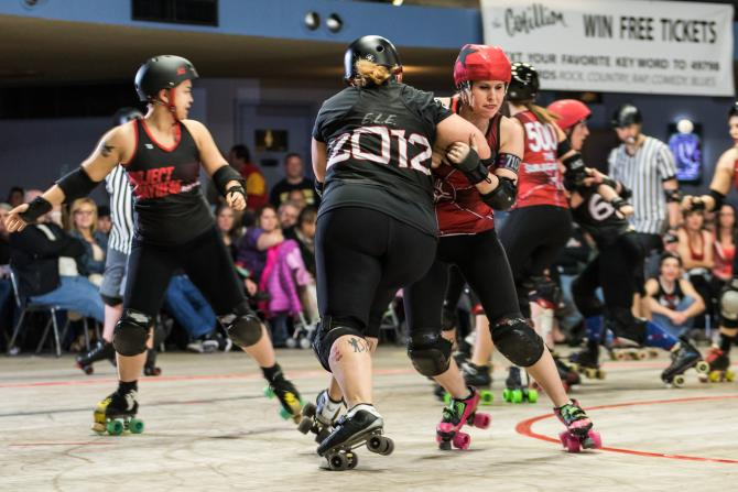 Two women battle it out on the skating rink during a roller derby match in Wichita
