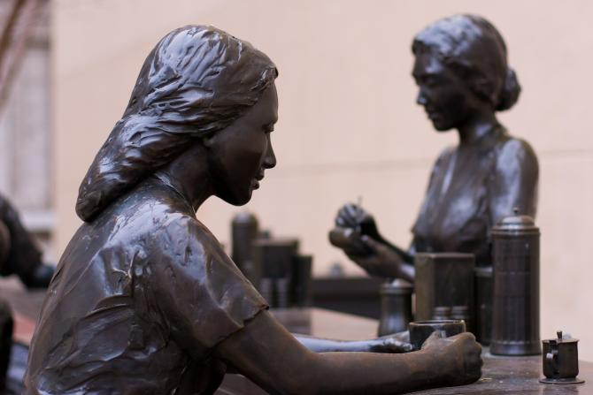 A bronze statue of a woman sitting at a bar top holding a mug commemorating the 1958 Dockum Sit-In as part of the Streetscapes Collection of statues in Wichita