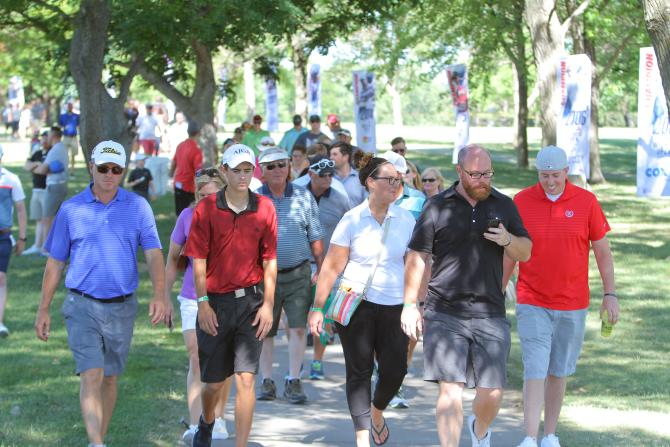 A crowd of people walk down a sidewalk towards the 17th hole at the Wichita Open