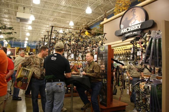 Three men discuss archery equipment at Cabela's in Wichita