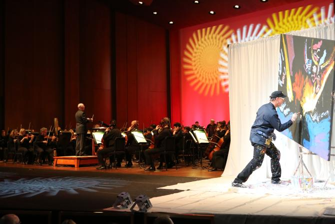 An artist paints on canvas in accordance with the Wichita Symphony Orchestra that plays behind him