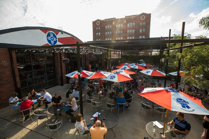 A sunny day greets a full patio of people eating and drinking at Pumphouse in Old Town