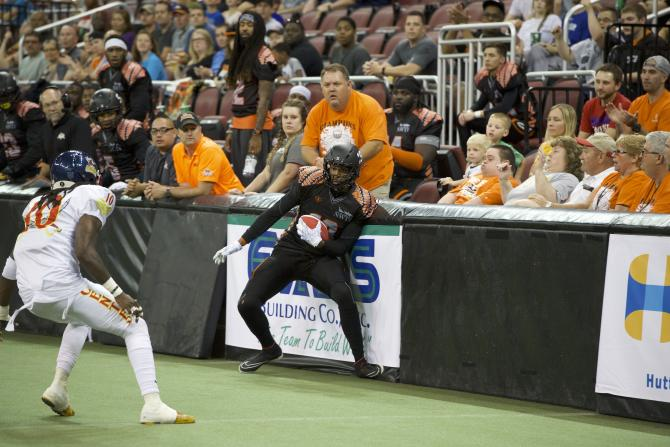 A Wichita Force Football player carries the ball along the wall towards the end zone