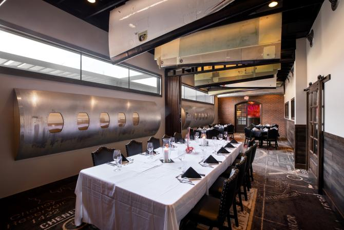 A dining room at Scotch and Sirloin sits empty with the tables set and new aviation decor on display
