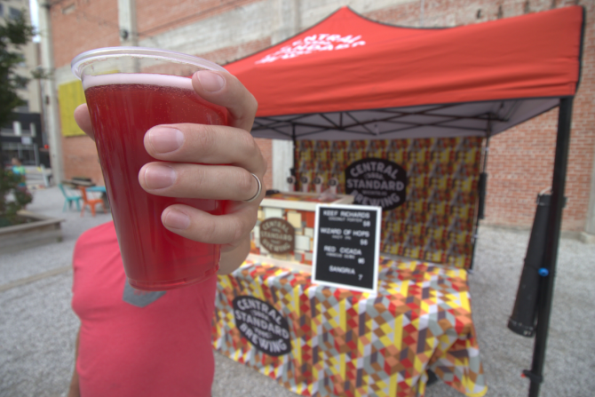 A man holds a beer towards the camera and blocking his face with a CSB booth behind him at the pop up park in Downtown Wichita