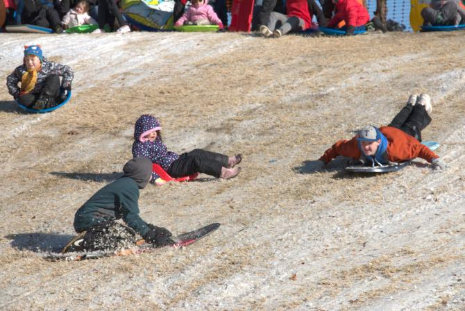 Kids sled down a hill at Wichita's Snow Day at the Mid-America All-Indian Center