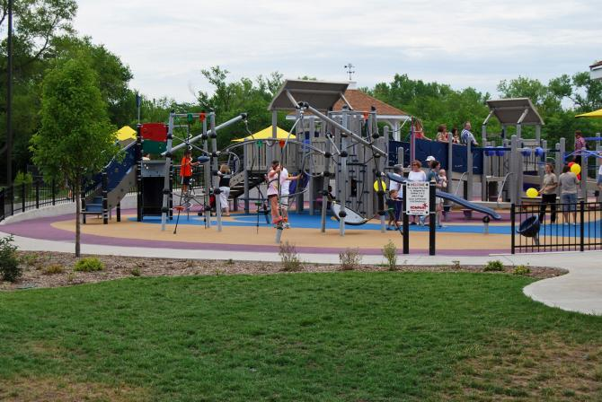 Kids play on a large play structure at Sedgwick County Park in Wichita on a clear day