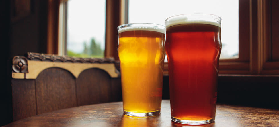 A red ale and a lager side by side on a table at the three legged crane pub.