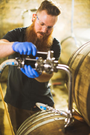 Wolf's Ridge head brewer Chris Davison working with barrels in brewery space