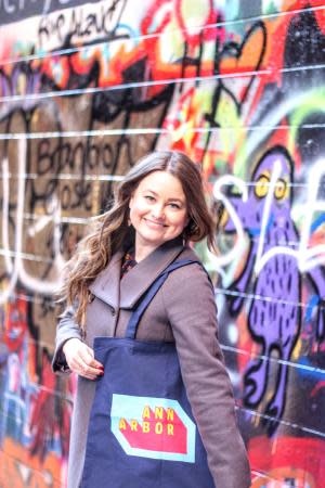 A woman stands in Graffiti Alley in Ann Arbor holding a reusable bag that features the Destination Ann Arbor logo.