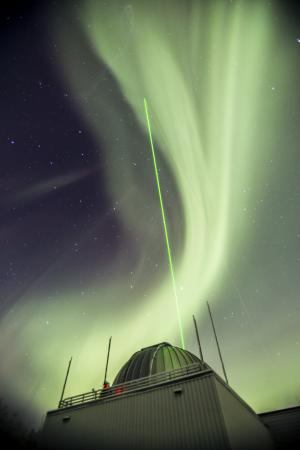 a green laser beam pointing into aurora-filled sky