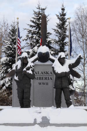 a statue of two servicemen standing in front of a large airplane propeller - memorial to US and Russia cooperation in World War II