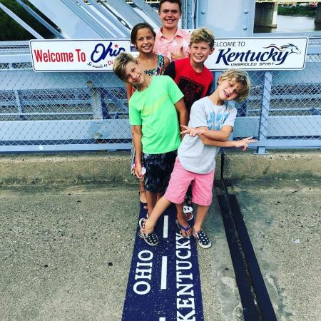 picture of five kids posing on purple people bridge in newport ky that links the states of ohio and kentucky