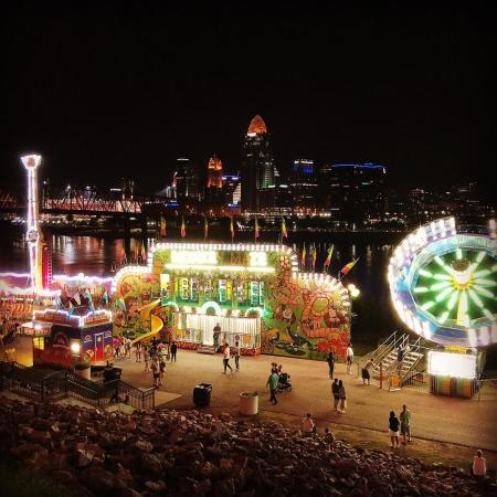 dark skyline behind illuminated food stand and festival rides during italianfest at newport ky