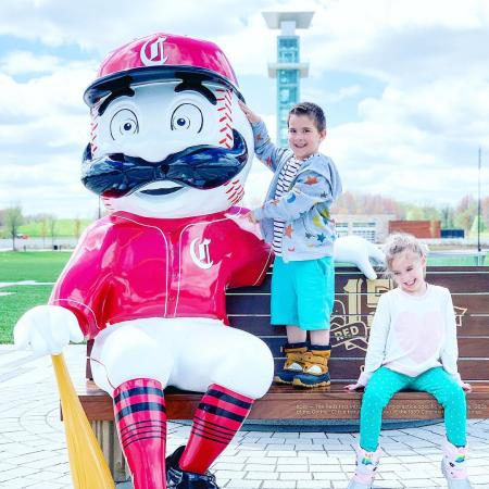 photo of the cincinnati reds mascot with two kids sitting on bench for 150th anniversary of major league baseball celebration in cincinnati oh