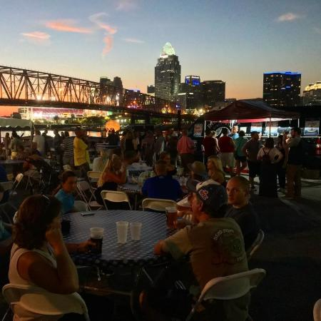 sunset at dusk with bridge and people enjoying drinks around a table during newport oktoberfest in newport ky