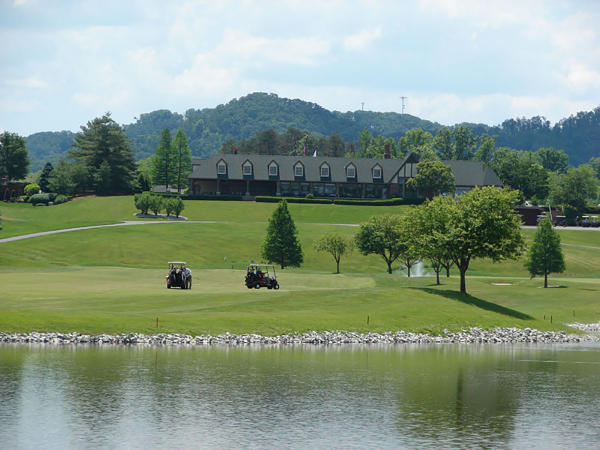 Club house, lake, and golfers on the course at Covered Bridge