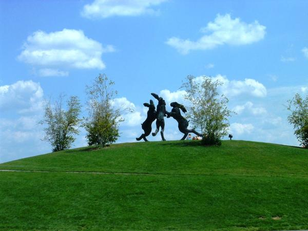 Three giant rabbit sculptures at the top of a grassy hill.