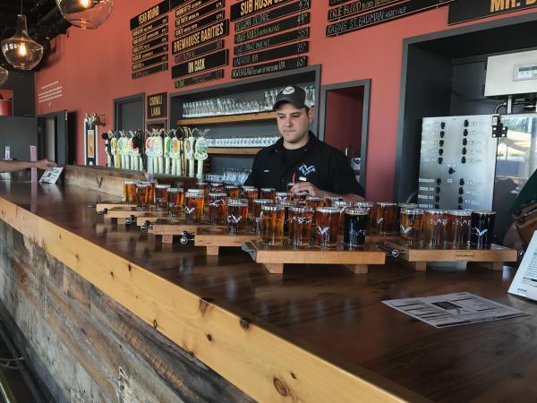 Bartender filling up beer flights at Flying Dog Brewery