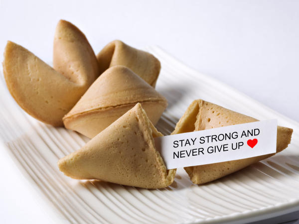 A handful of fortune cookies sit on a tray, with one cracked open and the fortune delivering encouraging words.