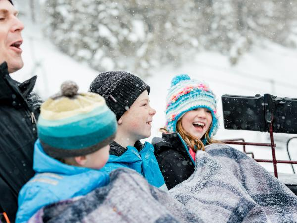 Dad and three children bundled up in a sleigh ride laughing