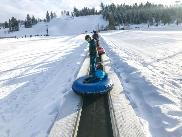 Boys riding up the hill on the magic carpet with tubes