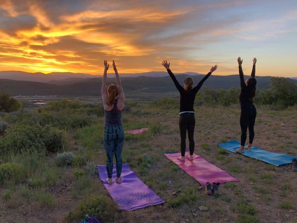 Three people doing yoga at sunrise