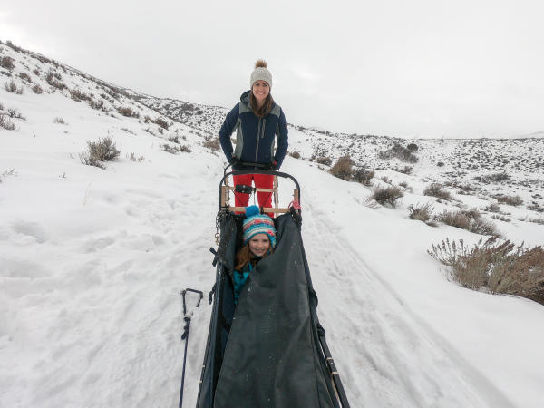Mother and Daughter pose for photo on the dog sled in the snow of Park City