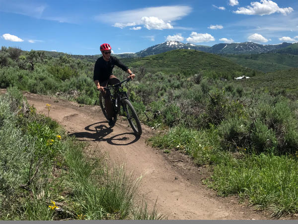 Guy Riding Mountain Bike with Mountains in Background