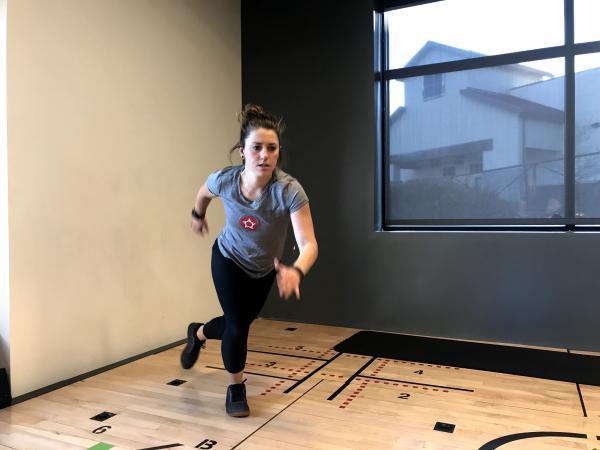 "Instructor demonstrating ""Skaters hold"" exercise"