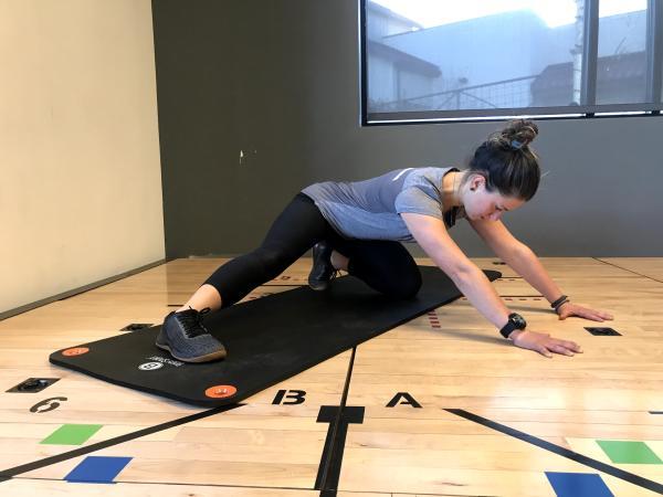 "Instructor demonstrating ""Adductor (inner thigh) rock back"" exercise"