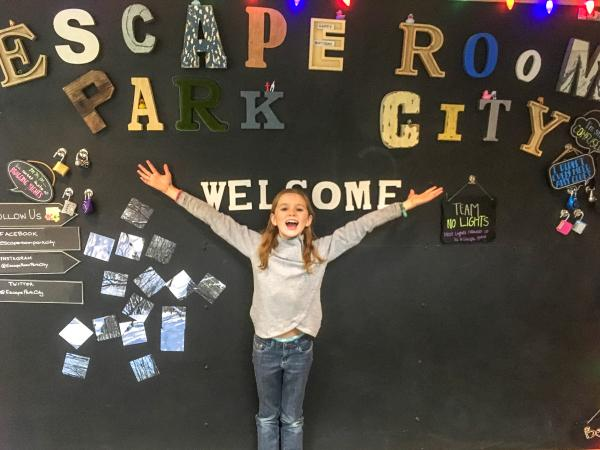 Girl stands in front of a sign that reads escape room