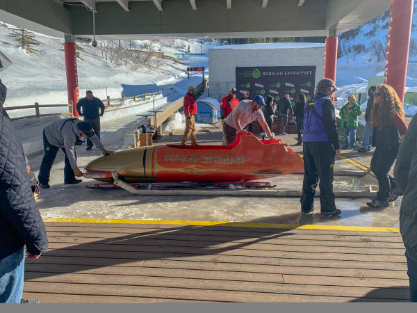People standing around while two people unload a bobsled off the track
