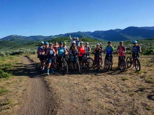 Women with mountain bikes pose for a group photo
