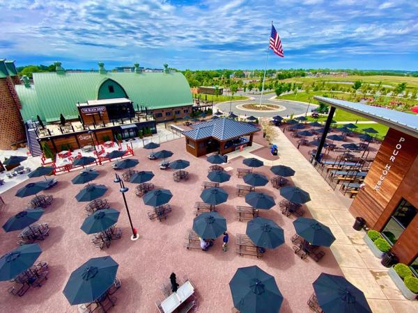 Aerial shot of Farm Brew Live Campus with social distancing of tables with black umbrellas spaced out.
