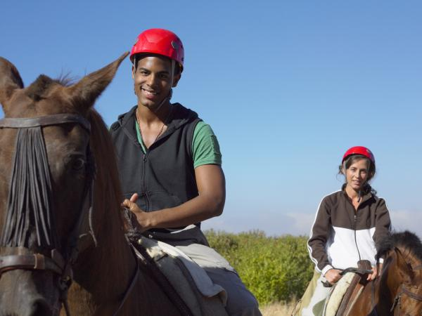 male and female riding horses on a trail