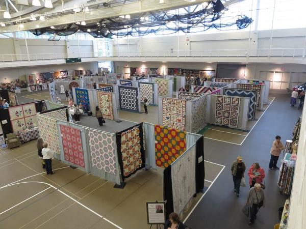 Quilts on display at a craft show.