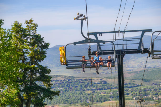 Family riding up a chairlift with alpine slide attached to chairlift