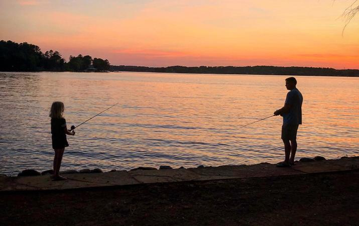 Father and daughter fishing at sunset on Lake Norman