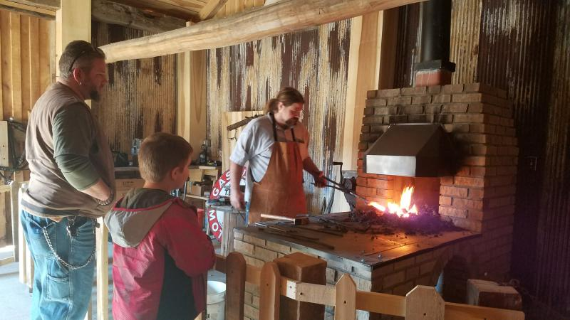 A father and son enjoy the blacksmith demonstration at Waverly Park.