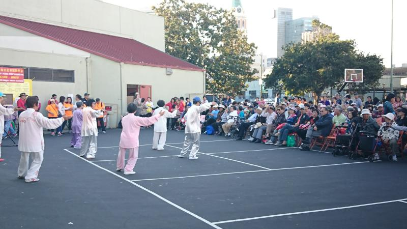 Tai Chi performers on the concrete in front of a Chinatown crowd