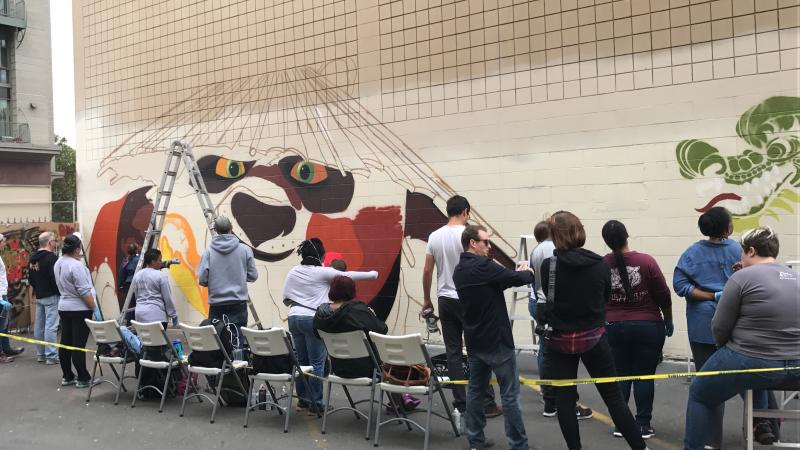 Volunteers Help Paint a Mural With Dragon School