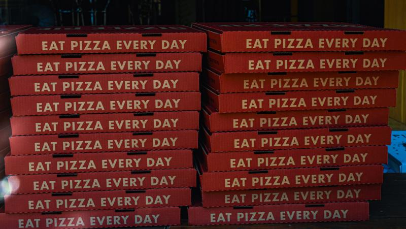 "Twenty large pizza boxes stacked on top of each other. Each box says ""eat pizza every day"". Photo by Melanie Griffin"