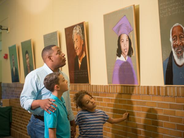 A father and two children admiring portraits at the Brown V Board Museum.