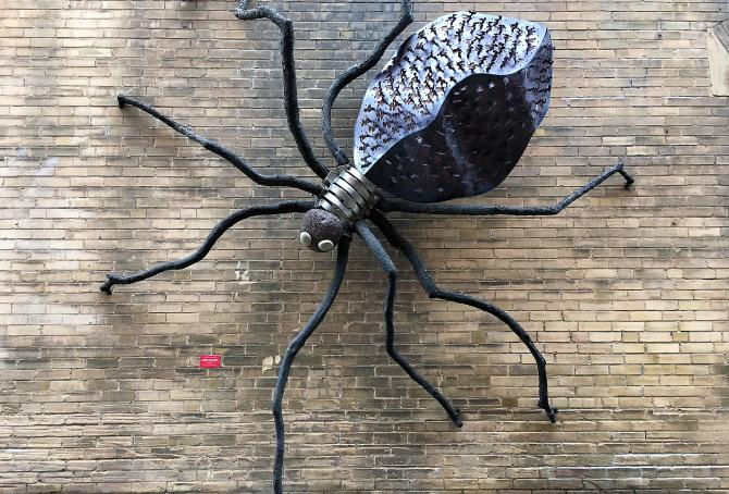 9-foot spider made of welded steel and rock climbing a brick wall