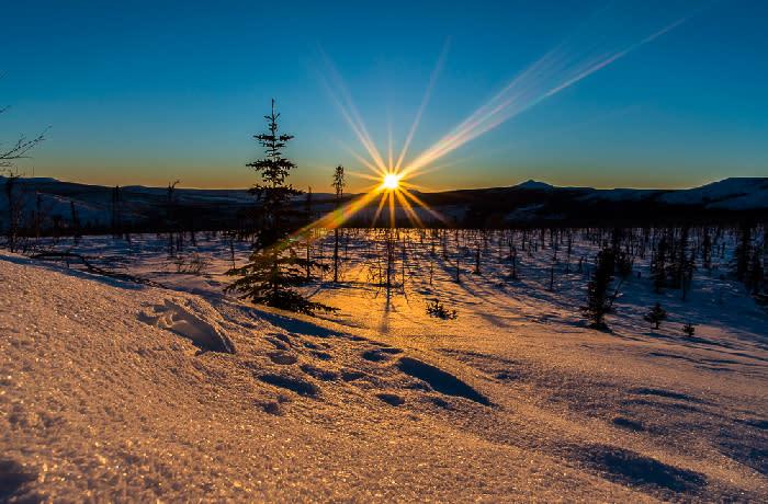 Solstice - Sun burst over snowy landscape