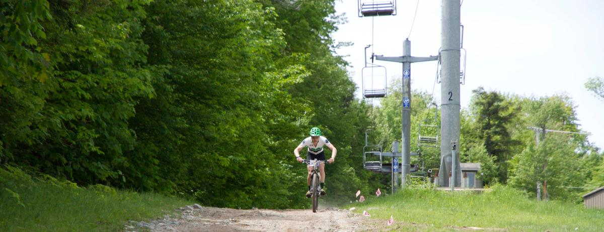 A man mountain bikes on a dirt path at Whiteface Mountain